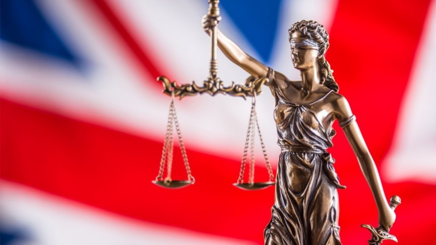 Justice is blind statue holding scales and sword, in the background blurry UK flag