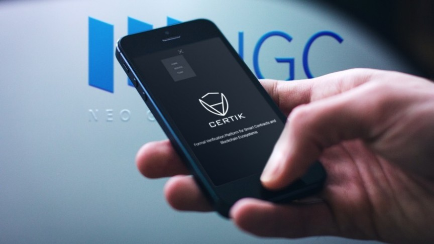 hand holding phone showing Certik name and logo, in the background NEO Global Capital (NGC) sign