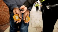 Man in handcuffs holding orange Bitcoins walking next to a police officer holding the cuffs, shot from behind