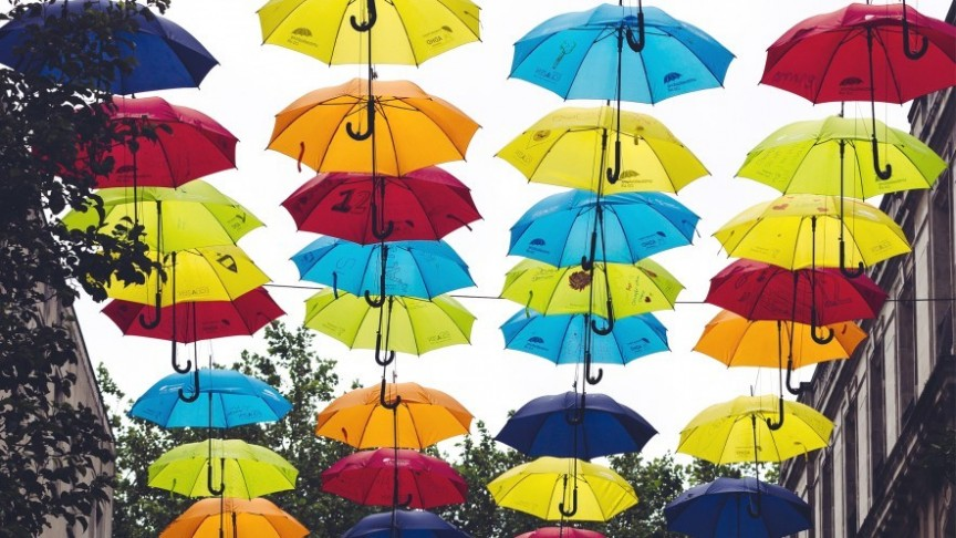colorful umbrellas hung above street, buildings and trees on both sides