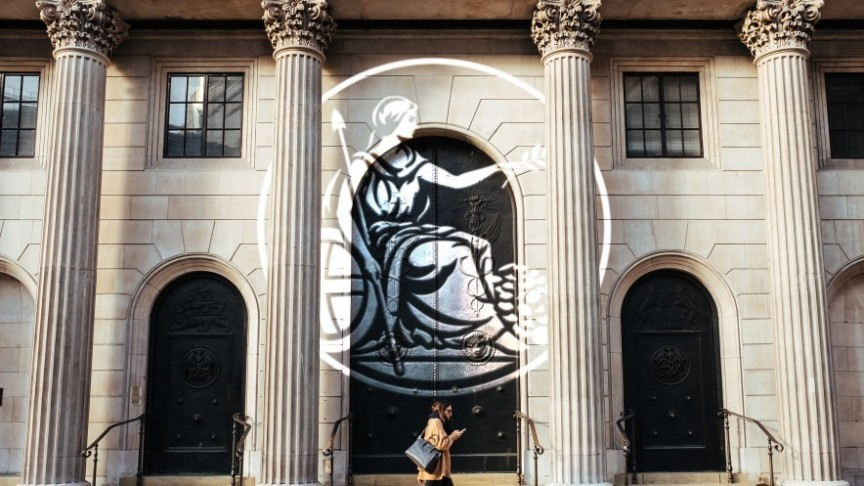 Bank of England, woman walking in front of building with phone, state imprint in the front