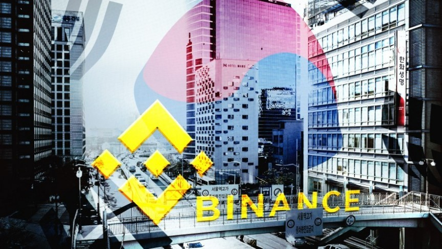 Binance name and logo in yellow on background of Korean street in black and white and blurry Korean flag in blue and red