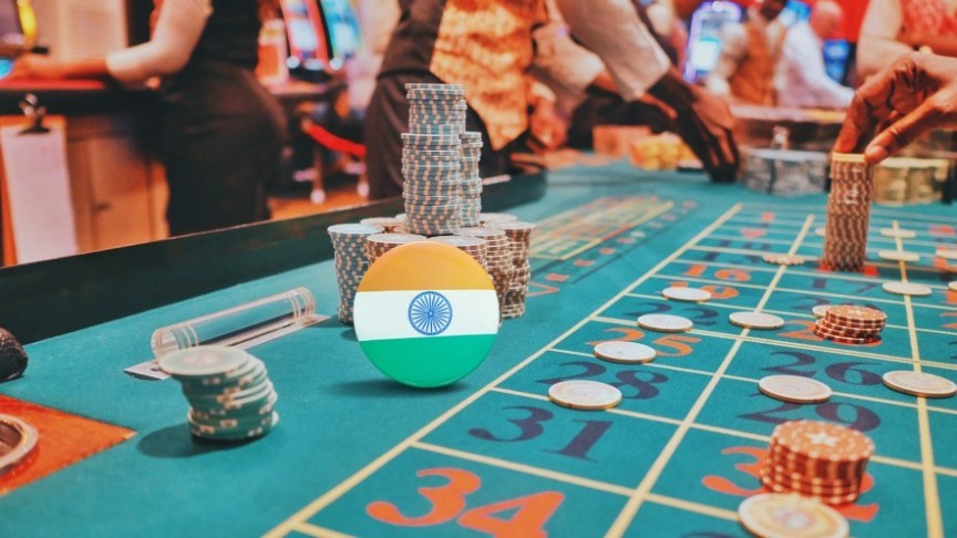 roulette table with chips, people around and a chip showing India's flag