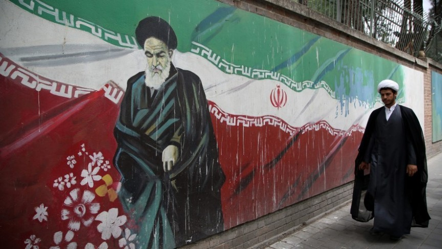 Iran's flag as a graffiti painting on wall, man walking in black robe