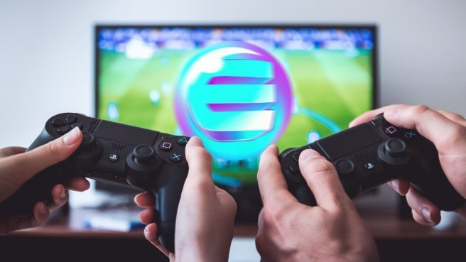 two sets of hands playing 2 PS4 controllers, TV screen showing football game and Enjin logo