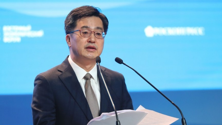 Hong Seong-ki in suit speaking in front of two speakers, blue background