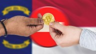 gold bitcoin changing hands, on background of stop sign and flags