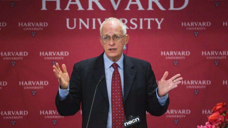 Oliver Hart in suit raising hands on red background of Harvard University wall