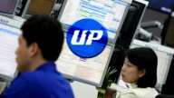 UPbit logo in blue on background of screens and two korean people