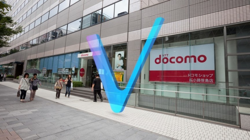 NTT Docomo translucent Logo on background of shopping center and people walking with shopping bags