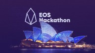 EOS Hackathon and EOS logo in white on background of lit Sydney Opera House at night