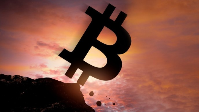 bitcoin logo falling off cliff on sunset background