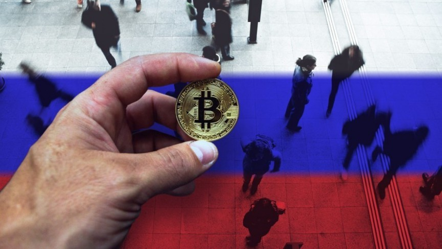 hand holding Bitcoin above train station with people walking, Russian flag colors on floor