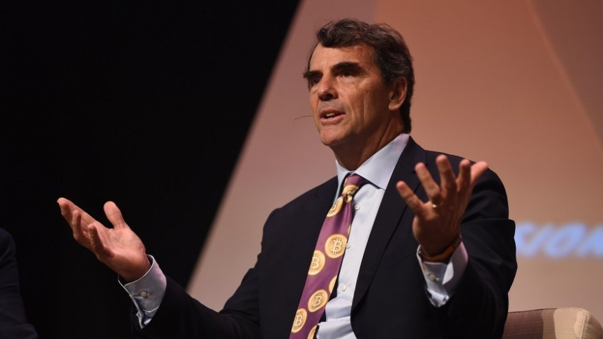 Tim Draper sitting with raised hands and suit and purple tie with Bitcoins