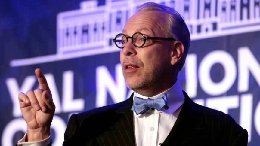 Jeffrey Tucker in suit and bowtie and glasses, pointing up
