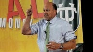 Jim Cramer in bright shirt and green tie, pointing and yelling